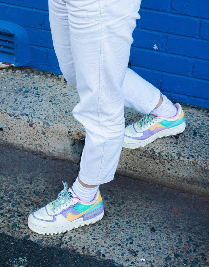 person in blue denim jeans and white green and pink nike sneakers