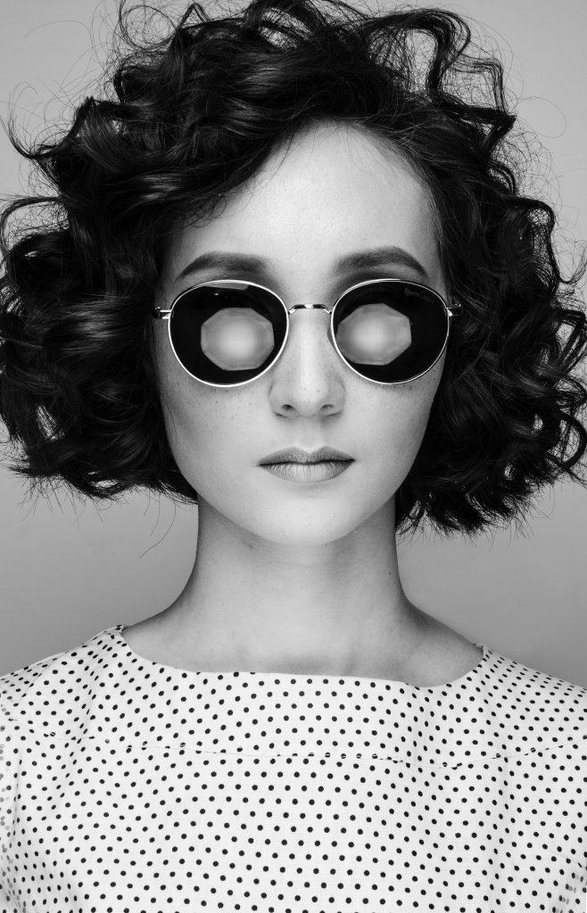 woman in white and black polka dot shirt wearing white framed sunglasses