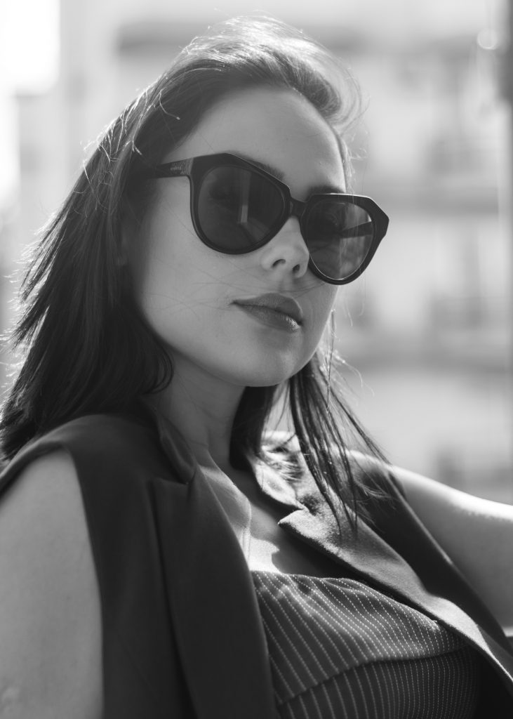 grayscale photography of woman wearing sleeveless blouse and sunglasses